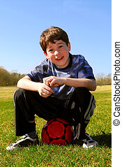 Boy with soccer ball - Young cute happy boy sitting on a red...
