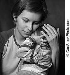 Tenderness - Mother gently embraces the crying child bw
