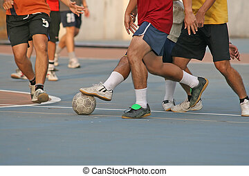 Street Soccer - Player makes a tackle during a game of...