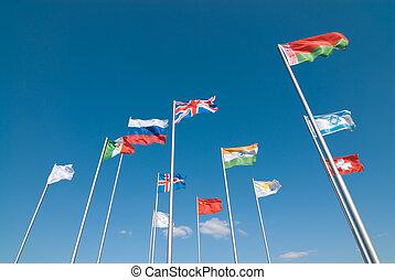 Flags waving across deep blue sky - International flags...