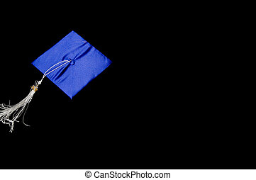 graduation cap flying through the air on black background