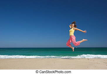 beautiful woman jumping in the beach