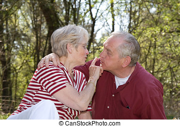 Loving gestures - Sweet elderly couple outdoors on a hot...