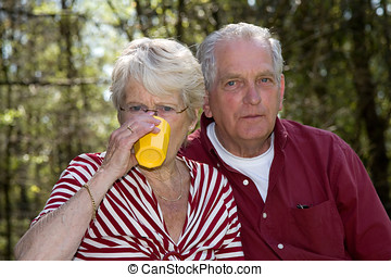 Having a drink - Elderly couple outdoors on a summer day...