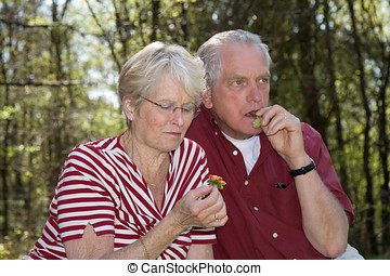 Healthy snack - Sweet elderly couple having a fruitsnack