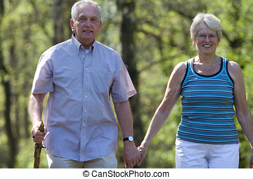Walking through the parc - Elderly couple walking through...