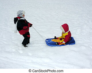 boy ride baby on sled