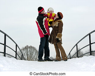 family with baby on winter bridge