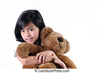 I love my Teddy Bear - Eight Year Old Asian Girl hugging her...
