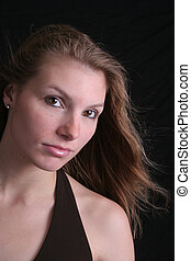 Woman hair blowing - A pretty woman in a black top has her...