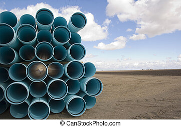 Agricultural irrigation piping stacked on farm