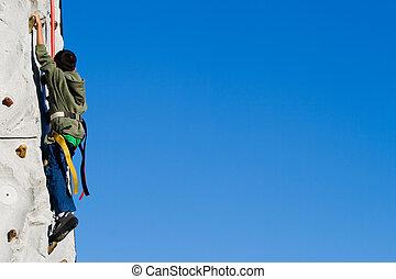 Wall Climbing - Young asian boy outside climbing on a rock...