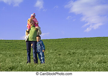 Family on the field in spring - Young woman and her children...