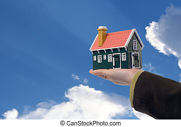 House in woman hand and sky - Miniature house in woman hand...