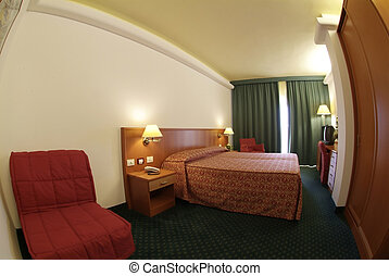 Hotel - An empty hotel room, with a bed and two lamps on the...