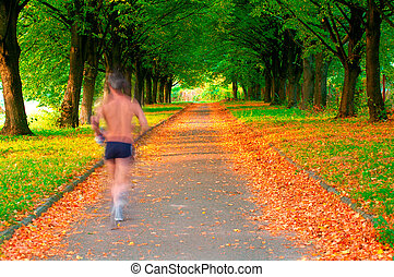 Runner in motion in a beautiful park - Runner in motion in a...
