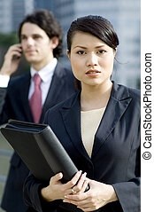 Business People Outside - A young asian businesswoman...