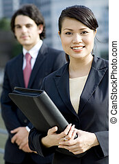 Business People - A young businesswoman standing outside...