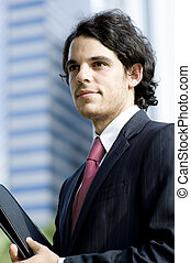 Businessman Outdoors - A young businessman standing outside...