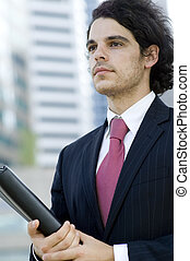 Businessman Outdoors - A young businessman holding document...