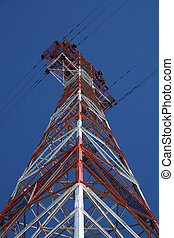Red and white electricity pylon against the blue sky