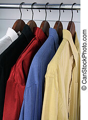 Colorful shirts on wooden hangers