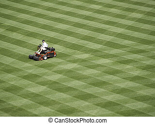 A lot to mow. - Workman readies a baseball field for the...