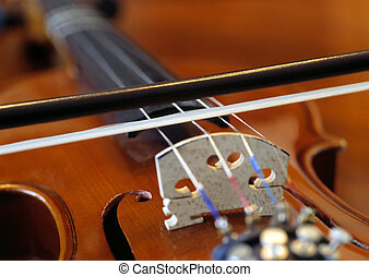 Violin and bow - Closeup of a bow on the strings of a...
