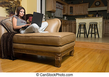 Surfing the net - Attractive woman sitting on beige leather...