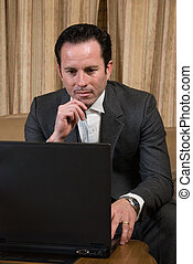 Man surfing the net - Man in business suit sitting on beige...