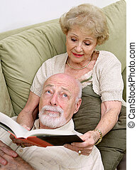 Reading to Bored Husband - A senior woman reading to her...