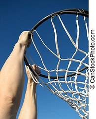 Playing basketball - Man reaching basketball hoop in a jump