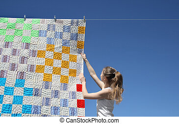 Girl and bright laundry - Girl touching a bright patchwork...
