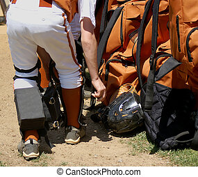 Catchers Gear - Boy putting shin guards on to prepare catch...