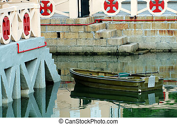 Rowboat - A rowboat anchored beside an antique quay