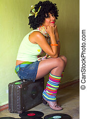 Cute curly disco girl on suitcase