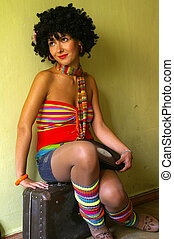 Cute curly disco girl sitting  on suitcase