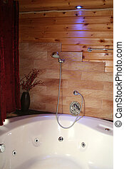 Wood Cabin Jacuzzi - A jacuzzi in a wooden cabin, lit with a...