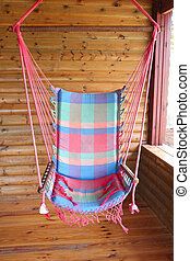 Cabin Porch Swing - A colorful swing hanging on the porch of...