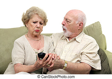 Seniors Fighting Over TV Remote - A senior couple fighting...