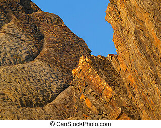 orange seaside rocks against the blue sky