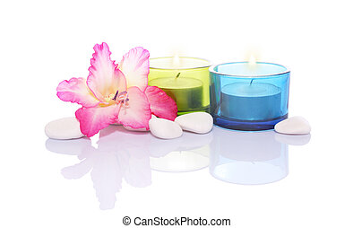 gladiola,candles and river stones with reflection on white...