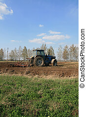 Agricultural work - Farmers plowing with tractor in...