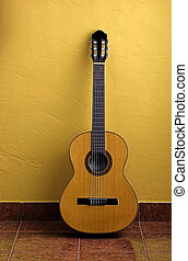 Guitar leaned to a yellow wall