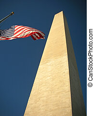 Washington Monument with the US flag on the National Mall.