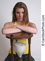 Woman and hour glass - A cute woman is resting her arms on...
