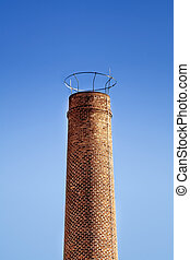 Chimney - Brick industrial chimney and clear blue sky as...