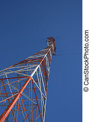 Red and white power tower in the blue sky
