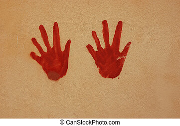 Hands on wall - Red hands painted on a wall with artistic...
