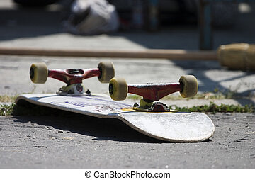 Skateboard - Overturned skateboard lying wheels up on the...